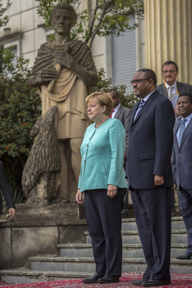German Chancellor Angela Merkel, center, and Ethiopia's Prime Minister Hailemariam Desalegn, right, inspect the honor guard at the national palace in Addis Ababa, Ethiopia Tuesday, Oct. 11, 2016. Merkel is visiting Ethiopia, where her meeting with Prime Minister Hailemariam Desalegn is expected to focus on the country's newly declared state of emergency, after months of protests demanding wider freedoms, and other issues including migration. (AP Photo/Mulugeta Ayene)