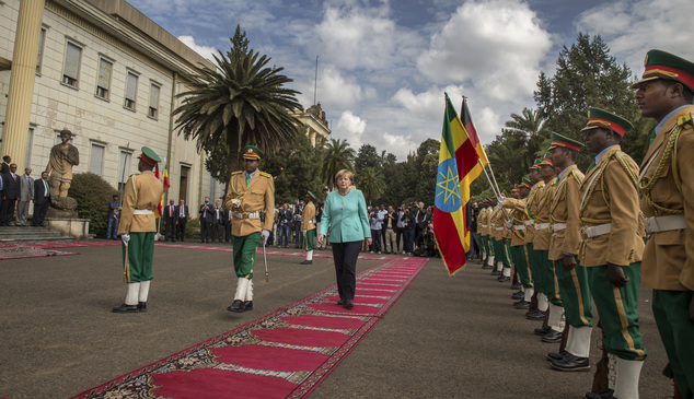 German Chancellor Angela Merkel, center, inspects the honor guard as she arrives at the national palace in Addis Ababa, Ethiopia Tuesday, Oct. 11, 2016. Merkel is visiting Ethiopia, where her meeting with Prime Minister Hailemariam Desalegn is expected to focus on the country's newly declared state of emergency, after months of protests demanding wider freedoms, and other issues including migration. (AP Photo/Mulugeta Ayene)